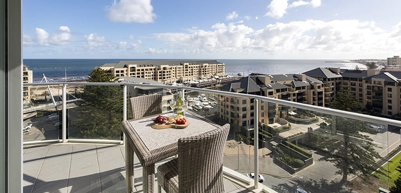 Glenelg hotels with vegan meal options on table on big balcony of 3 bedroom apartment with views of ocean and Glenelg beach in South Australia