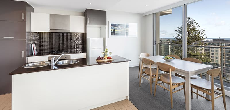 kitchen with big fridge, freezer, oven, toaster, kettle and dining room table in family friendly 3 bedroom apartment near beach at Oaks Liberty Towers hotel in Glenelg, South Australia