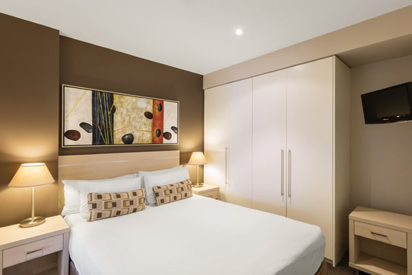 big bed with clean sheets and comfortable pillows in air conditioned 1 bedroom apartment with en suite bathroom at Oaks Plaza Pier hotel in Glenelg, South Australia