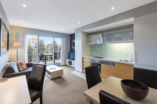 large open plan living room with modern furniture, Foxtel TV, private balcony and Wi-Fi access in 1 bedroom apartment at Oaks Plaza Pier hotel in Glenelg, South Australia