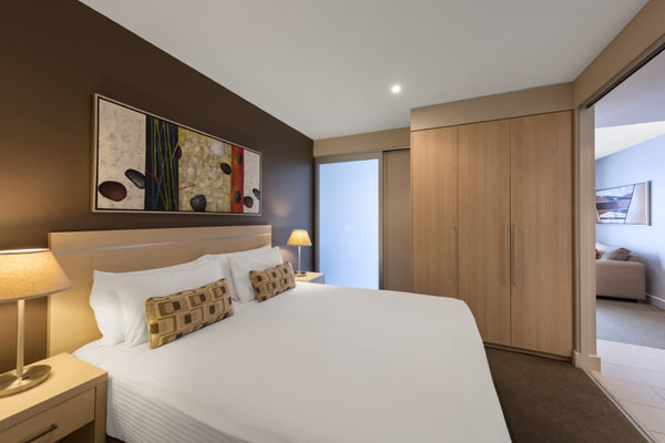 spacious bedroom with large storage cupboards, wardrobe and air conditioning in 1 bedroom ocean view apartment at Oaks Plaza Pier hotel near beach in Glenelg, South Australia