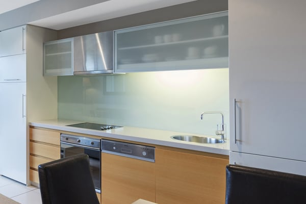 kitchen with microwave, oven, fridge, freezer and cupboards with cutlery in 1 bedroom apartment at Oaks Plaza Pier beachfront hotel in Glenelg, South Australia