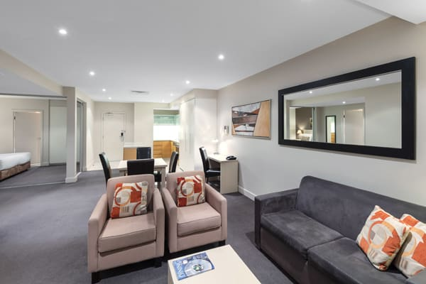 spacious living room with comfortable furniture, air conditioning, big mirror and kitchenette in 2 bedroom apartment at Oaks Plaza Pier hotel in Glenelg, South Australia
