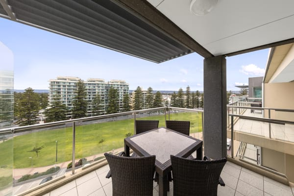 private balcony with table, chairs and view of public park at 2 Bedroom Apartment at Oaks Plaza Pier hotel in Glenelg, South Australia