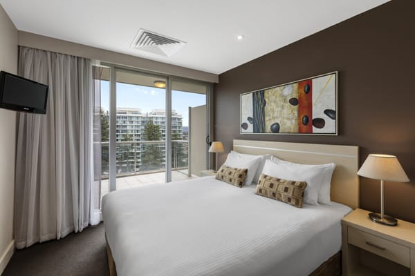 king size bed in bedroom with wall mounted TV and air conditioning in 2 Bedroom Apartment with private balcony at Oaks Plaza Pier hotel in Glenelg, South Australia