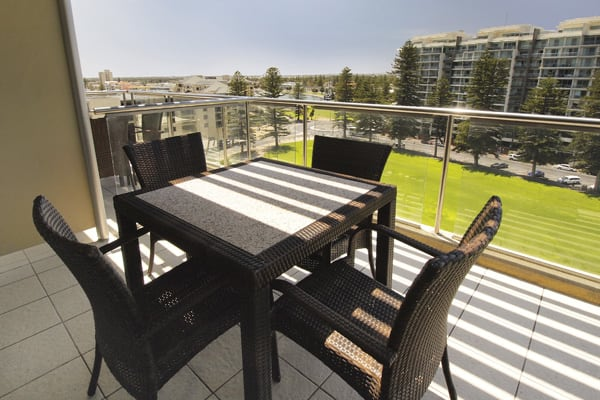 sun shining onto table and chairs on big private balcony of family friendly 3 Bedroom Apartment with view of sea at Oaks Plaza Pier hotel in Glenelg, South Australia