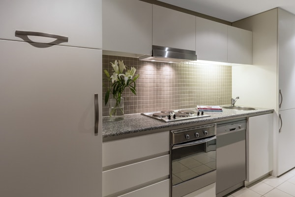 oven, fridge, freezer, dishwasher, toaster, kettle and cutlery on bench top in 3 Bedroom Apartment near Glenelg Beach in South Australia