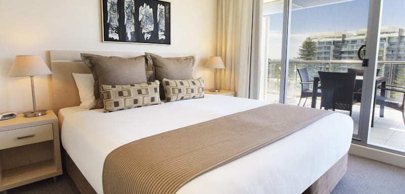 big queen size bed with clean sheets, pillows and private balcony outside at 3 bedroom apartment at Oaks Plaza Pier hotel in Glenelg, South Australia