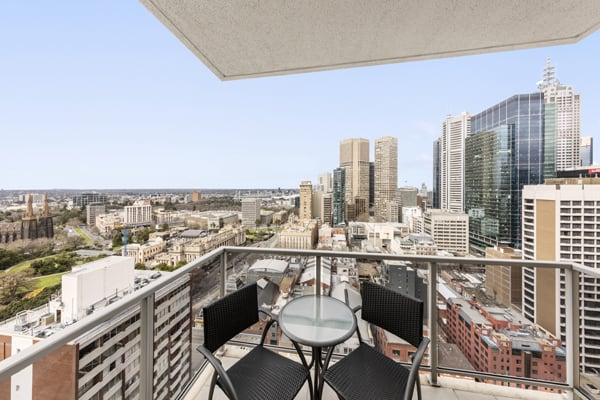 private balcony with table, chairs and views of Melbourne CBD from 1 bedroom apartment with air conditioning at Oaks on Lonsdale hotel in Australia