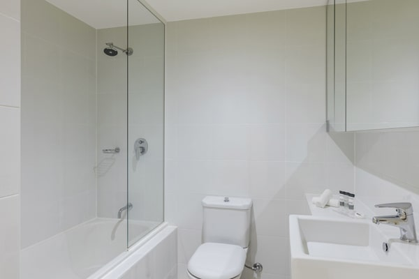 clean en suite bathroom of 1 bedroom hotel apartment with shower, toilet and bath tub at Oaks on Lonsdale, Melbourne city, Victoria, Australia