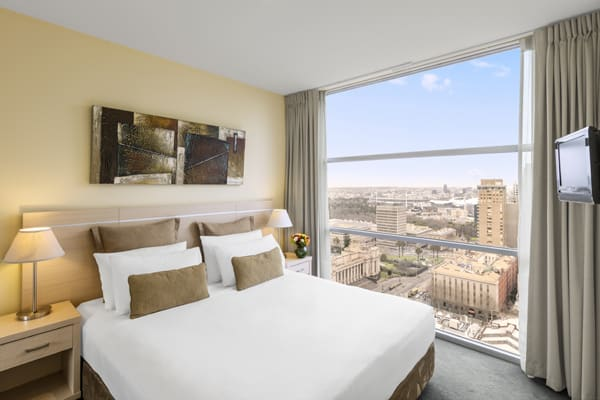 double bed in 1 bedroom apartment with large windows, Foxtel on TV and Wi-Fi access at Oaks on Lonsdale hotel, Melbourne city, Victoria, Australia