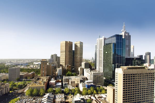 private balcony with table, chairs and city views of Melbourne CBD in 1 bedroom hotel apartment at Oaks on Lonsdale street