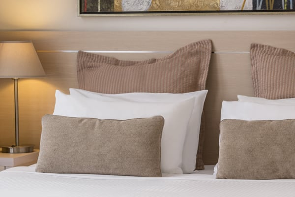 8 comfortable pillows on clean white bed sheets of queen size bed in 2 bedroom apartment at Oaks on Lonsdale hotel, Melbourne city, Victoria, Australia