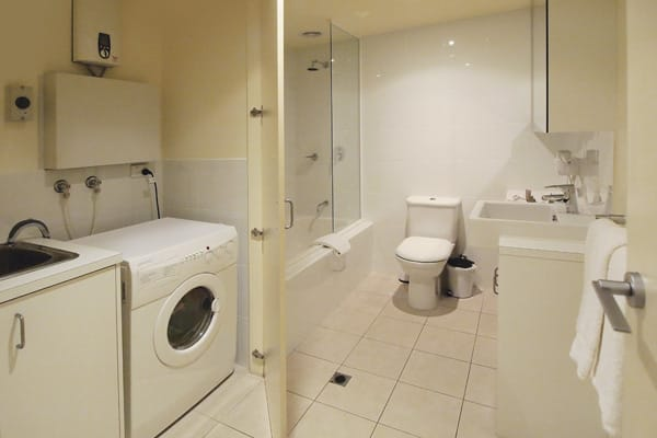 clean en suite bathroom with shower, bath tub, toilet, fresh towels and laundry facilities including washing machine and dryer in 2 bedroom apartment at Oaks on Lonsdale hotel, Melbourne city, Victoria, Australia