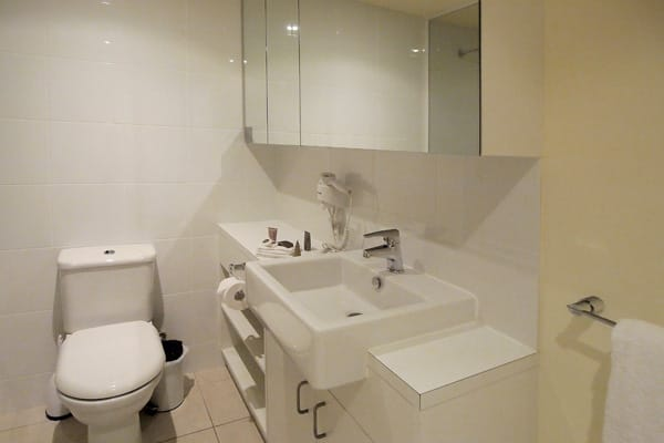 en suite bathroom with toilet, shower and mirror in Melbourne Hotel Apartments 2 Bedroom accommodation for corporate travellers visiting Melbourne CBD, Victoria, Australia