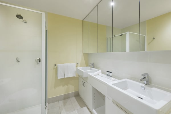 disabled access shower, toilet and clean towels in en suite bathroom of 2 Bedroom Executive Apartment for business travellers at Oaks On Lonsdale hotel in Melbourne city centre, Victoria, Australia