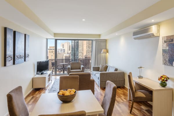 large living room with air conditioning in serviced apartments Melbourne CBD with Wi-Fi access, work desk for business travellers, TV with Foxtel and private balcony outside with views of Melbourne city skyline
