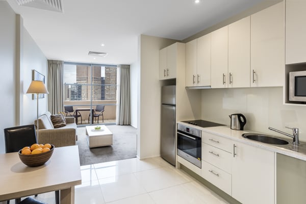 open plan Hotel Apartment in Melbourne city with microwave, fridge and kettle in kitchen and air conditioned living room at Oaks On Lonsdale