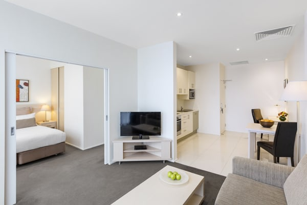 air conditioned living room with Wi-Fi, TV with Foxtel, comfortable couches and table in Hotel Apartment at Oaks On Lonsdale in Melbourne city, Victoria, Australia