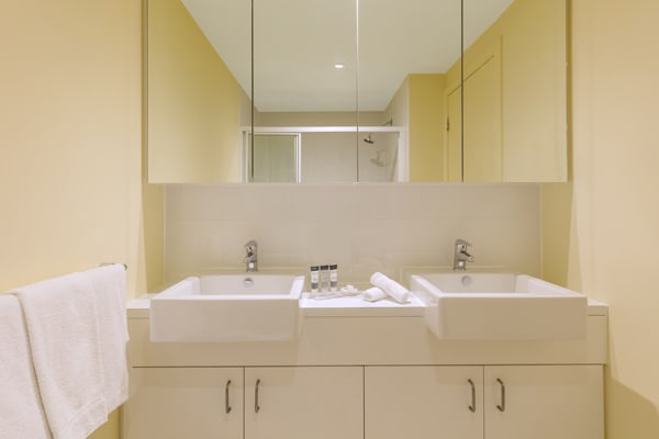 big mirror in en suite bathroom with toilet and shower in hotel Studio Apartment at Oaks On Lonsdale in Melbourne city, Victoria, Australia