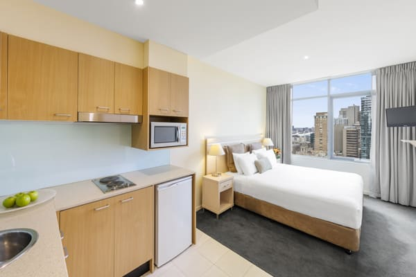 kitchenette with bar fridge and microwave adjacent to bedroom of Studio Apartment at Oaks On Lonsdale hotel with free Wi-Fi in Melbourne city, Victoria, Australia