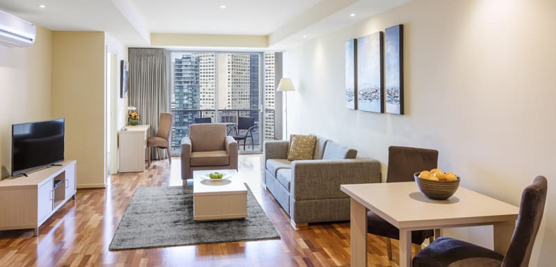 large, air conditioned living room with Foxtel on TV, Wi-Fi, modern furniture and private balcony with views of Melbourne CBD in 3 Bedroom Apartment at Oaks On Lonsdale hotel in Victoria, Australia
