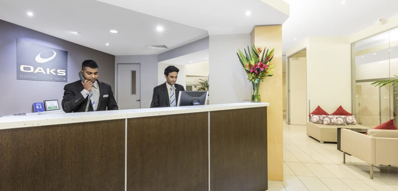 friendly hotel staff greeting hotel guests in reception foyer of Oaks On Lonsdale in Melbourne city, Victoria, Australia