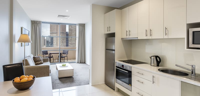 interior of air conditioned serviced apartments Melbourne CBD with comfortable couches and kitchenette with microwave, big fridge, freezer and kettle in Hotel Studio Apartment at Oaks On Lonsdale in Melbourne city, Victoria, Australia