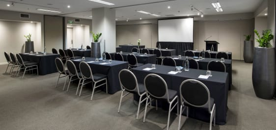 row of tables and chairs in big conference venue for hire in Melbourne CBD with projector screen at front of the room
