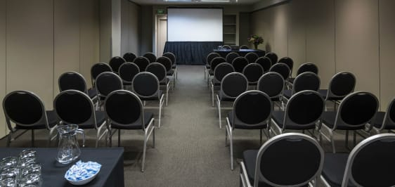 row of chairs and table with catering food with projector screen at front of events room for hire in Melbourne city