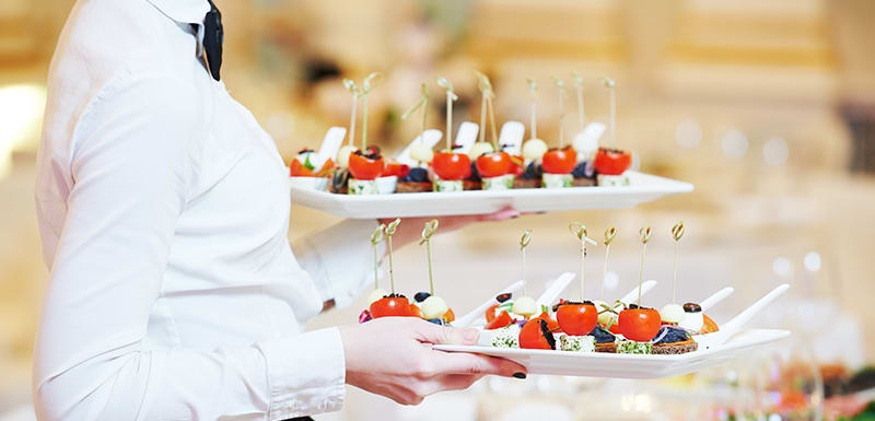 waitress from catering staff serving vegetarian canapes at conference event at Oaks on Market hotel in Melbourne city, Victoria, Australia