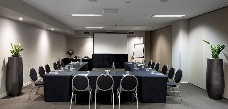 tables and chairs in meeting room for hire in Melbourne city with projector at front and Wi-Fi access for guests