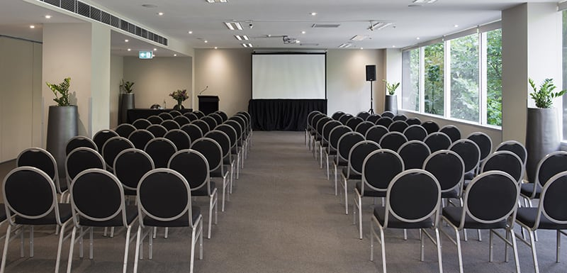 long rows of chairs in front of large projector screen in conference room venue for hire in Melbourne city, Victoria, Australia