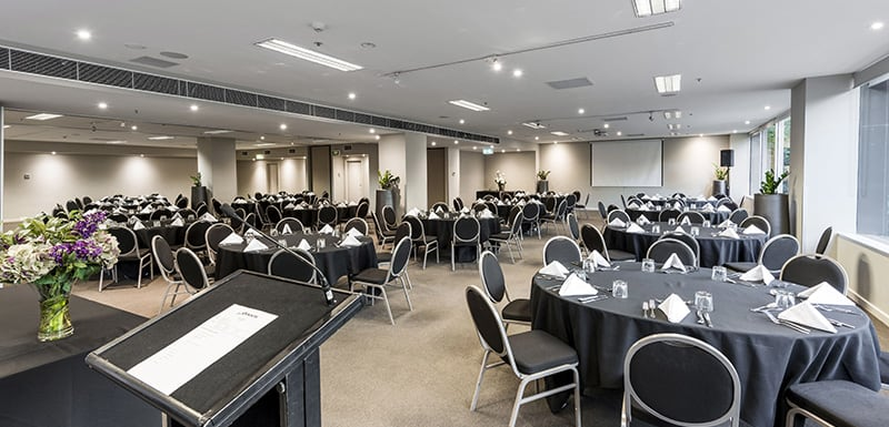several round tables and chairs in large functions room for hire in Melbourne city with air conditioning and Wi-Fi access for guests