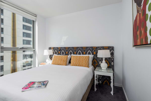 Double bed next to big windows with view of Melbourne city centre in 1 bedroom apartment at Oaks South Yarra hotel, Victoria, Australia