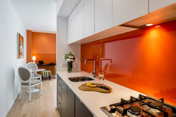 kitchen area with stove cook top, microwave and kettle in 1 bedroom apartment with free Wi-Fi access at Oaks South Yarra hotel, Melbourne city, Victoria, Australia