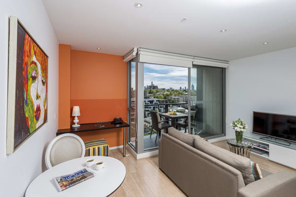 big living room with Foxtel on TV, private balcony with views of Melbourne city in 1 bedroom apartment at Oaks South Yarra hotel, Victoria, Australia