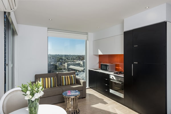 open plan living room and kitchenette area with microwave, Wi-Fi, comfortable couches and private balcony outside of hotel Studio Apartment at Oaks South Yarra, Melbourne city, Victoria, Australia