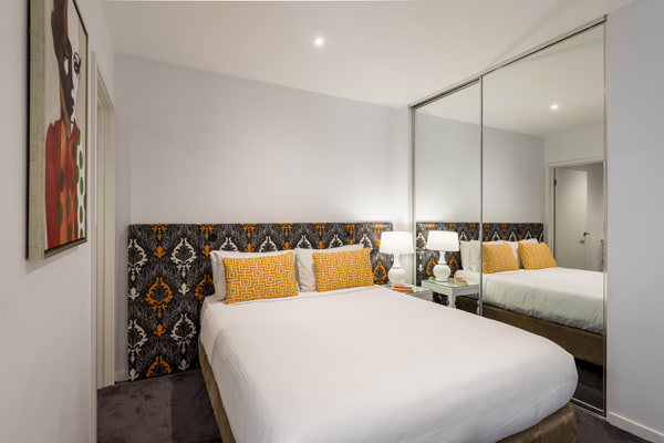 double bed in large bedroom of hotel Studio Apartment with Wi-Fi in Melbourne city at Oaks South Yarra, Victoria, Australia