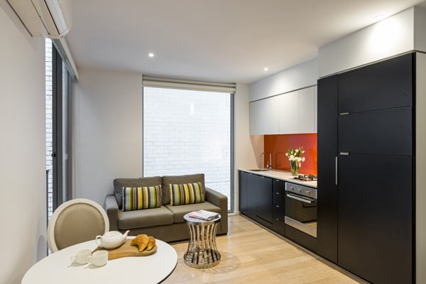 open plan living room with kitchenette that has microwave, oven, toaster, kettle and dining room table in Studio Apartment at Oaks South Yarra hotel, Melbourne city, Victoria, Australia
