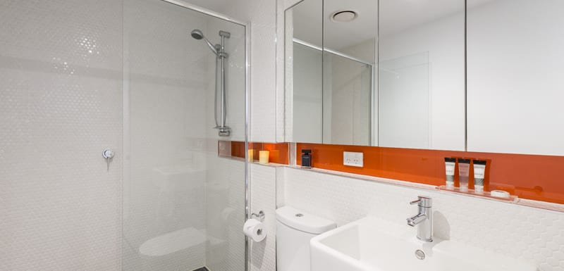 clean en suite bathroom of 1 bedroom apartment with adjustable shower, toilet and clean towels at Oaks South Yarra hotel, Melbourne city, Victoria, Australia