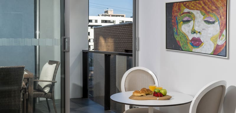 vegan menu options on table in living room of large hotel Studio Apartment with private balcony and Wi-Fi for corporate travellers visiting Melbourne city on business trips