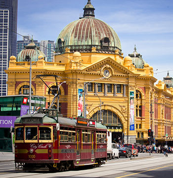 Flinders St Station in Melbourne in summer time with tram passing and blue skies in background