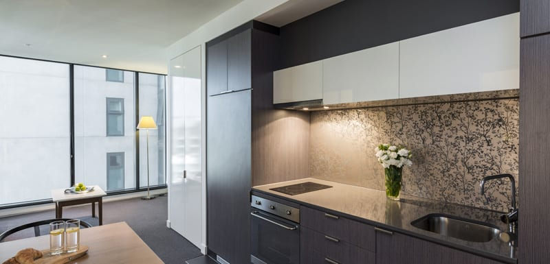 kitchen with modern appliances, microwave, stove, kettle, toaster and cutlery in hotel studio apartment in Melbourne city