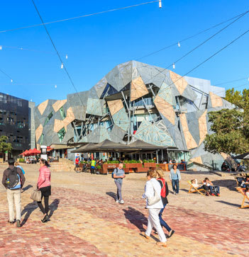 Couple on romantic holiday walking through Federation Square looking at buildings in summer in Melbourne city, Australia