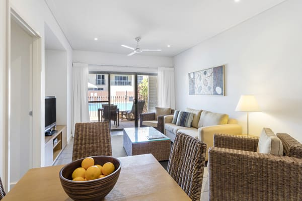 lounge room with ceiling fan, modern furniture, Foxtel on TV and air conditioning in 1 bedroom apartment at Oaks Broome hotel, Western Australia