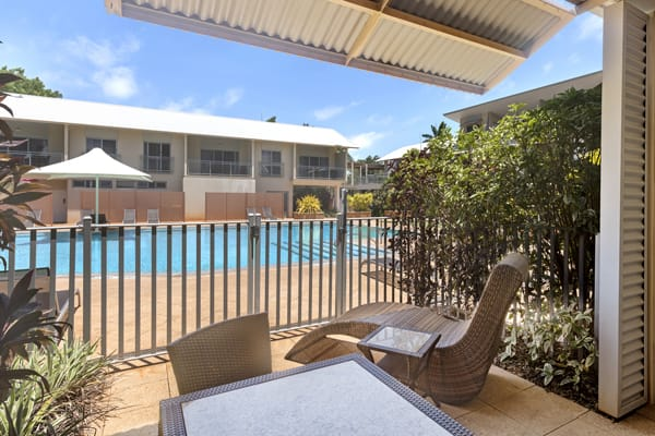 furnished private courtyard with sun loungers next to swimming pool outside 1 bedroom apartment at Oaks hotels Broome, Western Australia