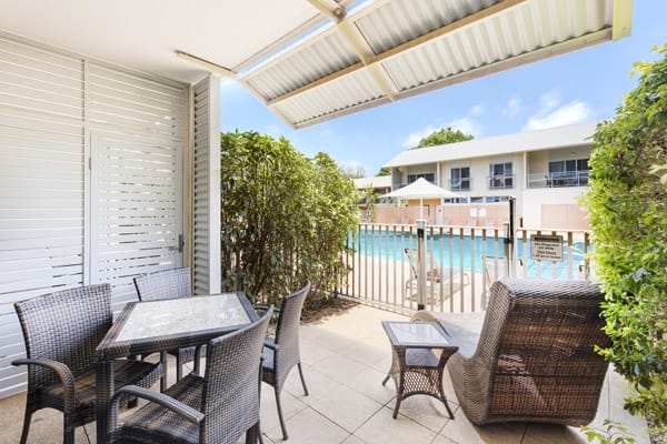 table, chairs and sun lounger on shaded private balcony outside 1 bedroom poolside apartment at Oaks Broome hotel, Western Australia