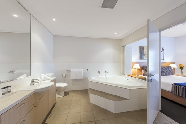 large en suite bathroom with spa hot tub, toilet and big mirrors in air conditioned 1 bedroom apartment at Oaks Broome hotel, Western Australia