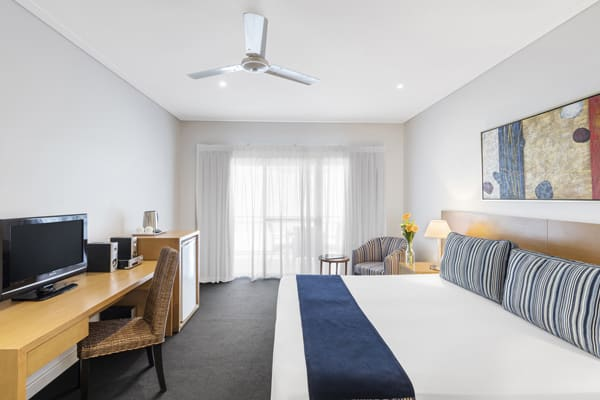 large, comfortable double bed in air conditioned hotel bedroom with ceiling fan in Broome, Western Australia